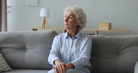 doubt : Pensive thoughtful old elderly woman looking away thinking of future feeling lonely worried, serious single melancholic senior adult grandma waiting sit alone on sofa at home, loneliness concept