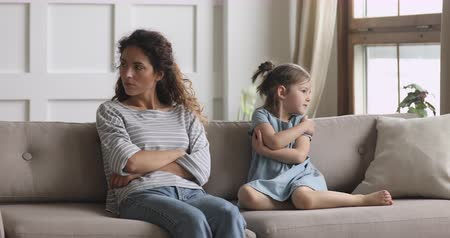 аргумент : Unhappy stubborn young adult mother and little small child daughter turn back sit on couch ignore each other feel angry not talking after family conflict fight, parents and children argument concept Стоковые видеозаписи