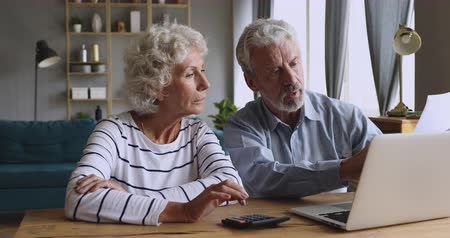 banking document : Serious happy senior retired old grandparents couple calculate domestic bills to pay online using laptop app and calculator discussing manage bank loan insurance payment together sit at table at home