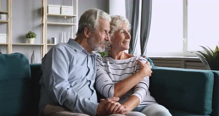 keresik : Happy elderly senior couple looking away in future talking relaxing sit on couch, smiling old adult grandparents embracing feel optimistic thinking hoping planning retirement together concept at home