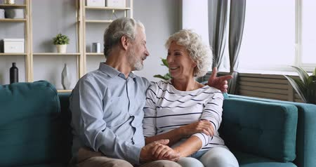 together trust : Happy elderly senior grandparents couple chatting embracing holding hands relaxing sit on couch at home, old retired family talking enjoy bonding retirement lifestyle lounge on sofa in living room