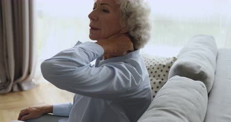 artrit : Tired upset senior elderly old woman grandmother feeling stiff sore neck pain concept rubbing massaging tensed muscles suffer from fibromyalgia ache problem stretching sit on sofa at home. Stok Video