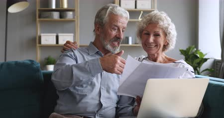 calcular : Happy old couple talking checking papers holding domestic bills and laptop computer, satisfied bank clients senior grandparents customers planning budget investment loan insurance payment at home Vídeos