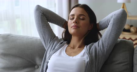 breathing fresh air : Serene attractive young woman resting on couch taking deep breath of fresh air holding hands behind head, healthy calm lady relaxing on comfortable sofa napping feel stress free at home lounge alone Stock Footage