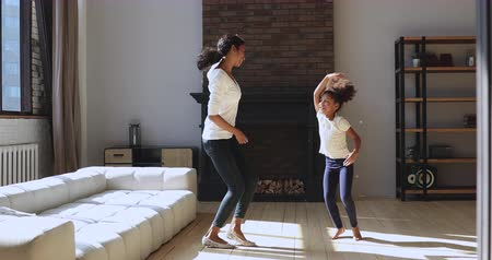 sağlıklı yaşam : Funny active african mom nanny and cute preschool kid daughter jumping dancing together in modern living room, happy mixed race family young mother with child girl laughing feel carefree at home Stok Video