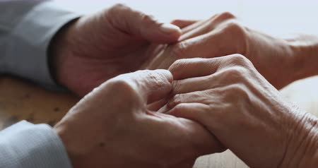 lasting : Senior old adult family couple holding hands together, older husband stroking elderly wife arms, lasting grandparents love in marriage relationship concept, help care support and trust, close up view Stock Footage