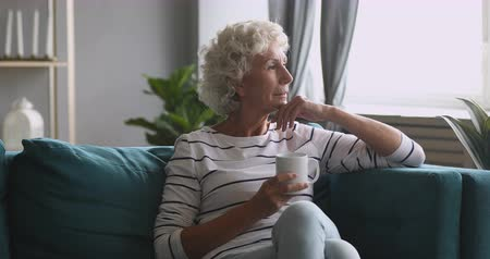 сомнение : Serious thoughtful old senior woman looking away drinking tea thinking of future feeling anxious worried, pensive elderly adult grandmother sitting alone on sofa holding cup and dreaming at home