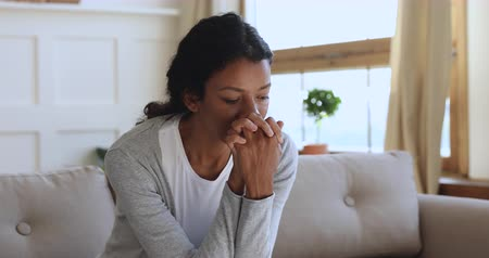 etnia africano : Anxious thoughtful worried african american woman sit on sofa looking away feel depressed doubtful, upset stressed sad young lady think of psychological problem regret mistake make difficult decision Stock Footage