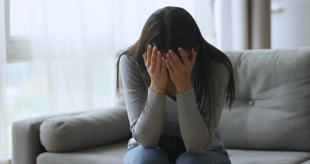 jealous : Upset depressed young woman crying alone on sofa at home feel desperate about problem and hurt, sad stressed girl troubled with abortion, frustrated by unwanted pregnancy, regret bad mistake concept Stock Footage