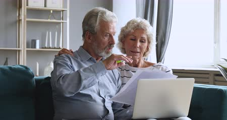 számla : Serious old retired couple holding papers and laptop checking domestic bills planning finances expenses pay online, senior grandparents manage household payments doing paperwork sit on sofa at home Stock mozgókép
