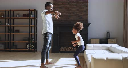 babysitter : Happy active african father having fun with small kid girl copy imitate funny moves in modern living room interior, carefree family dancers dad and cute little child daughter playing together at home Stock Footage