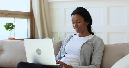 etnia africano : Smiling mixed race lady sit on couch using laptop notebook at home, happy young african american woman typing on computer browsing surfing internet look at screen having fun chatting in social media