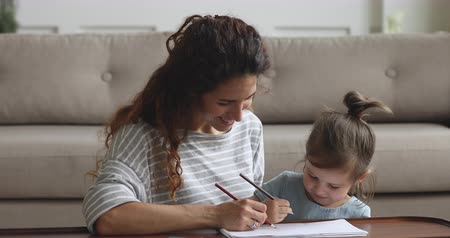 babysitter : Happy family young mom nanny and cute preschool child daughter enjoy creative hobby coloring picture together, smart kid girl learn drawing with pencils helping mother, children development concept