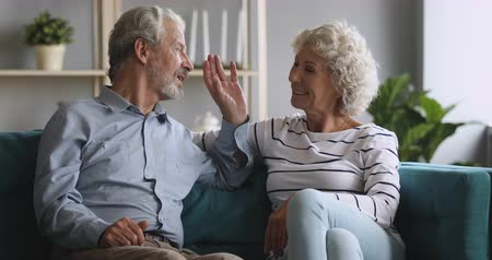 honesto : Happy senior old grandparents couple relaxing talking laughing sitting on couch at home, elderly mature family enjoy trust honest conversation flirting chatting bonding lounge on sofa in living room
