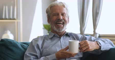 tevreden : Happy elderly senior man with wide dental smile sitting on sofa holding hot drink cup, positive old grandfather relaxing alone at home drinking tea looking at camera laughing posing for portrait
