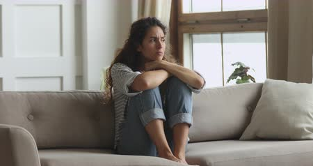 decidir : Thoughtful sad worried young woman sit alone on couch embracing knees troubled with loneliness, depressed lady feel upset jealous regret mistake abortion, having psychological mental problem concept