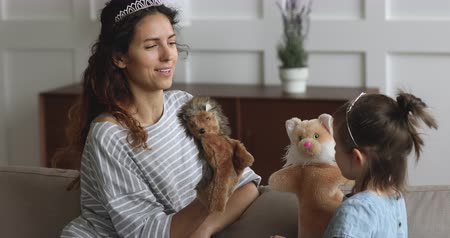 marionet : Playful happy young mum babysitter wearing crown holding puppet toys on hand talking laughing playing with cute little preschool daughter telling fairy tale having fun together sit on sofa at home