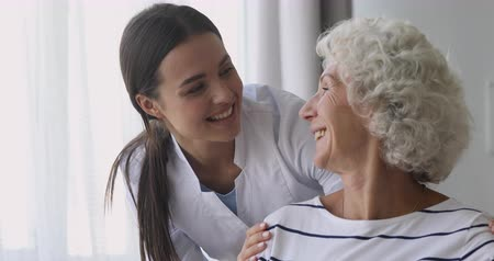 caregiver : Happy young woman nurse caretaker helping talking with senior grandmother patient give support empathy, female doctor carer having trust conversation with elderly lady, older people homecare concept