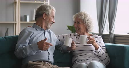 honesto : Happy old senior couple holding drinking tea talking laughing sit on sofa, honest smiling elderly adult grandparents family husband and wife chatting bonding having fun relaxing together at home