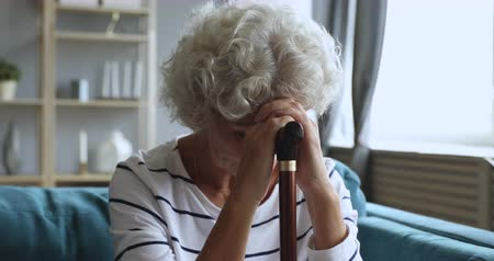 luto : Sad tired lonely senior lady patient hold crutch walking cane stick sit alone on couch wait help, upset depressed disabled old granny having health problem miserable about disability grieving concept Stock Footage