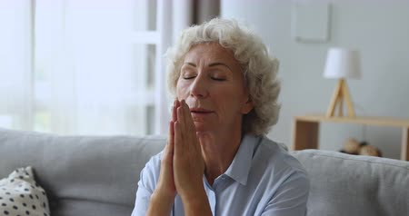感謝 : Faithful old senior grandmother pray with hope faith holding hands together sit on sofa alone at home, religious elderly woman believer christian with eyes closed say gratitude worship prayer concept 動画素材
