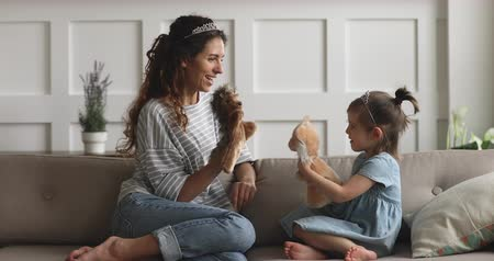 loutka : Happy family young mom babysitter or nanny wearing crown holding toys having fun with cute small child daughter sit on sofa, mother queen and little kid girl bonding playing puppets together at home