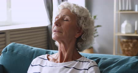 очиститель : Calm elderly old lady relaxing doing breathing meditation exercises on sofa, serene happy senior grandma lounge in living room enjoying fresh purified air at home concept feel stress free rest alone Стоковые видеозаписи