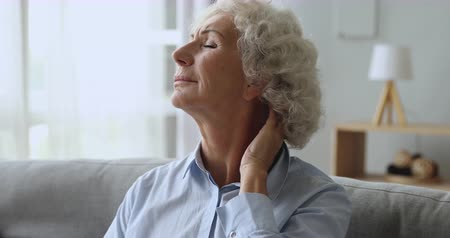 artrit : Unhappy tired senior old woman rubbing neck feeling pain sit on couch at home, upset elderly grandma massaging stiff muscles suffering from osteoarthritis osteochondrosis fibromyalgia ache concept Stok Video