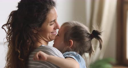 bağ : Affectionate family mother embrace cute little adopted child daughter bonding cuddling feeling love, happy foster care parent young mom hugging adorable kid girl holding toy enjoy connection concept Stok Video