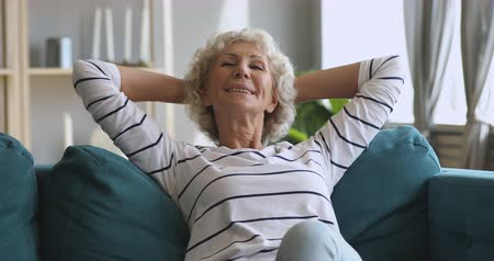 lélegzet : Happy relaxed senior old woman resting alone dreaming sitting on comfortable sofa, calm mindful elderly grandma relaxing breathing fresh air feel no stress holding hands behind head at home Stock mozgókép