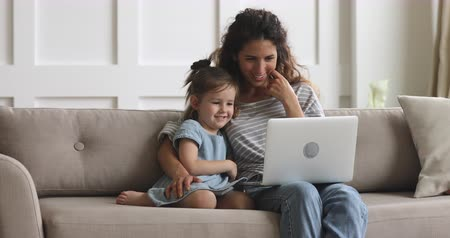 conferencing : Happy parent mother and cute small child daughter looking at laptop screen webcam having fun using funny face mask effects making conference video call chat at home relaxing laughing sitting on sofa Stock Footage
