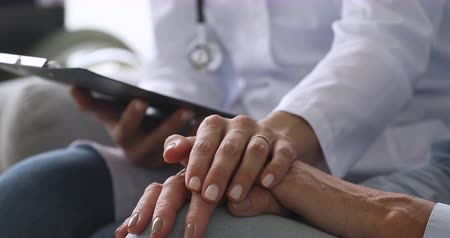 demencia : Female nurse doctor wear white uniform hold hand of senior grandmother patient help express empathy encourage tell diagnosis at medical visit, older people healthcare support concept, close up view Archivo de Video