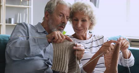 вязание : Focused funny elderly senior grandfather learning knitting helping older wife grandmother teaching husband handiwork hobby craft holding needles talking relaxing together at home sitting on sofa.
