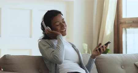 playlist : Smiling african ethnic girl wearing wireless headphones listening mobile music on phone singing song with eyes closed relax sit on sofa, happy young woman holding cell enjoy using player app at home