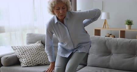 artrit : Upset worried senior adult woman feel sore back ache getting up from sofa, tired elderly grandma touching spine suffer from osteoarthritis lower lumbago spinal backache, older people backpain concept Stok Video