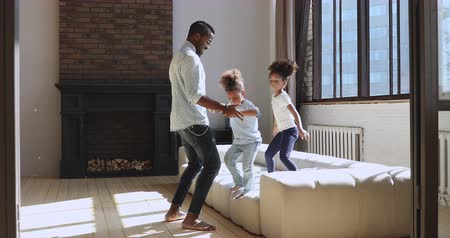 babysitter : Active funny young african american father playing game having fun with cute small kids siblings at home, carefree happy dad and little son daughter hold hands dancing spinning in modern living room