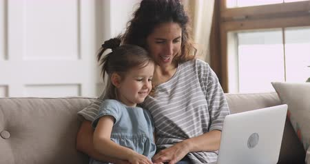 preschool : Happy family young mom and preschool little kid child daughter having fun using laptop together looking at screen talking by webcam app conference call watching cartoons online sit on sofa at home Stock Footage