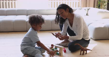 babysitter : Happy young african mom babysitter playing game with small kid son sit on warm heated floor, female nanny mother and little child boy holding dinosaurs having fun with toys and wooden blocks at home Stock Footage