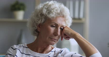 luto : Sad thoughtful mature old adult woman looking away feeling depressed, pensive senior elder granny sit alone at home think of lonely future waiting for support upset about solitude melancholy concept Stock Footage