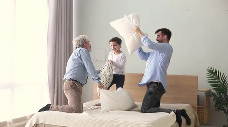 multigenerational : Grandfather son and grandson spend active free time having fun at home hold cushions playing pillow fight on bed three 3 different generation warm relations intergenerational family connection concept