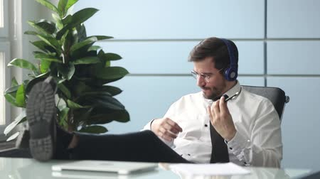 imaginární : Businessman resting in office room workplace put legs on table leaned on chair wearing headphones imitating playing a guitar enjoy listen music during break, stress relief, hobby or relaxation concept Dostupné videozáznamy