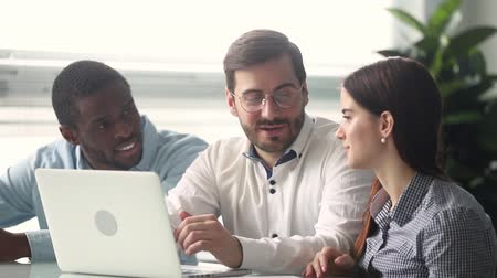 internar : Diverse colleagues become familiar with new pc software sitting together at office desk talking discuss enterprise business online apps on laptop feels happy, teamwork multi racial friendship concept