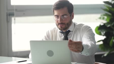 босс : Focused male entrepreneur working makes notes writing down information typing corporate email on laptop communicating online with client using software solve business issues sit at office desk alone