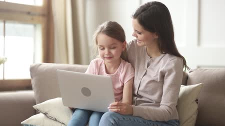 nanny : Mom sitting on couch with preschool daughter using laptop for educational purposes broadcast, nanny and kid girl watch cartoon funny video, modern tech, parental control, activities with child concept