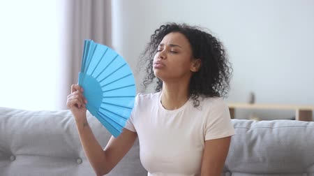 preciso : African overheated exhausted young woman sitting on couch in living room at home feels hot waving blue fan annoyed with high temperature apartment without climate control and air conditioner concept