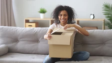 fidedigno : Happy mixed race woman sitting on couch in living room hold on laps box opens unpack received arrived big carton parcel feels satisfied, easy fast trustworthy transportation delivery service concept
