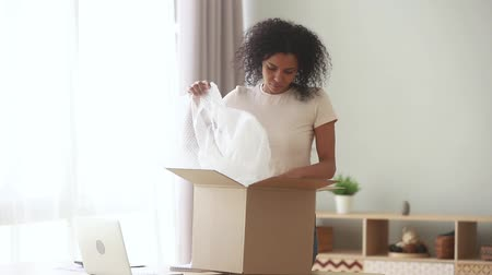 postacı : African woman standing in living room at home received from postman carrier parcel, client of postal delivery services opens big carton box feels dissatisfied broken goods arrived damaged item concept