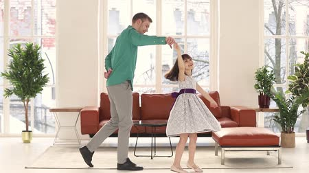 şükran : Father holds hand of daughter swirls her, family dancing together in light cozy living room, loving dad standing on knee thanking cute kid girl for dance kissing arm people having fun at home concept Stok Video