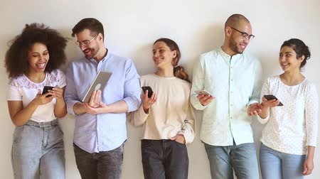 gruppo di persone : Positive multi-ethnic millennial people girls guys holds electronic gadgets standing against beige wall talking laughing, generation addicted with devices, modern tech everyday usage, new apps concept Filmati Stock