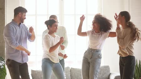 sentir : Active diverse cheerful friends listen favourite track moving dancing in living room enjoy life and free time together fool around laughing, multi-ethnic friendship like-minded people have fun concept